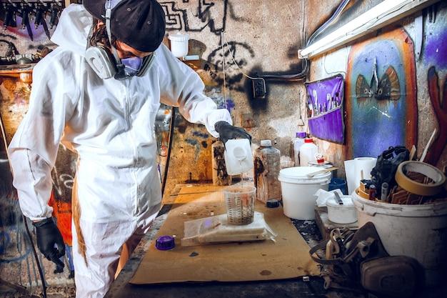 Mestre pintor em fábrica - pintura industrial em madeira com pistola. Foto gratuita