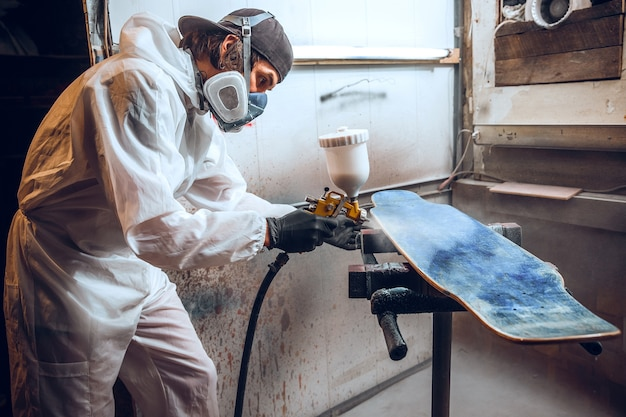 Mestre pintor em fábrica - pintura industrial em madeira com pistola Foto gratuita