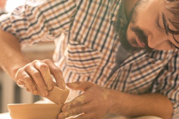 Mestre preciso da cerâmica usando uma esponja para suavizar as bordas do pote de barro enquanto trabalha sobre um dos itens de cerâmica Foto Premium