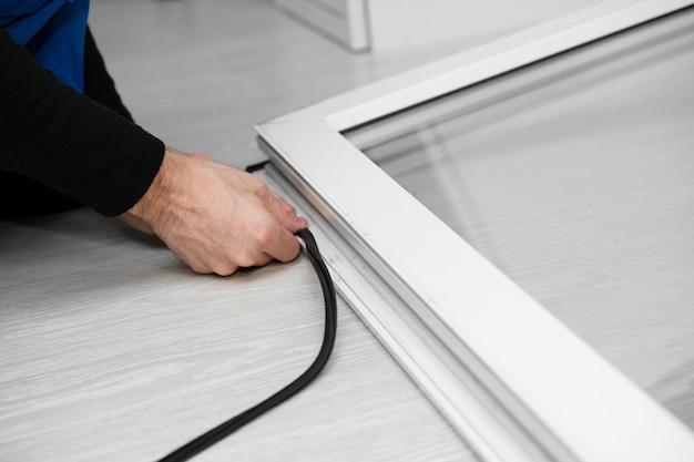 Mestre profissional na reparação e instalação de janelas, muda a junta de vedação de borracha nas janelas de pvc Foto Premium