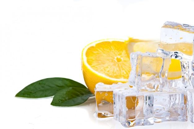 Metade de um limão fresco, brilhante, com folhas verdes e cubos de gelo frio Foto Premium