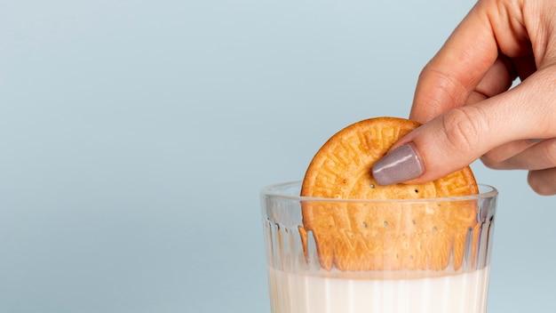Metade do biscoito mergulhado em um copo de leite e copie o espaço de fundo Foto gratuita