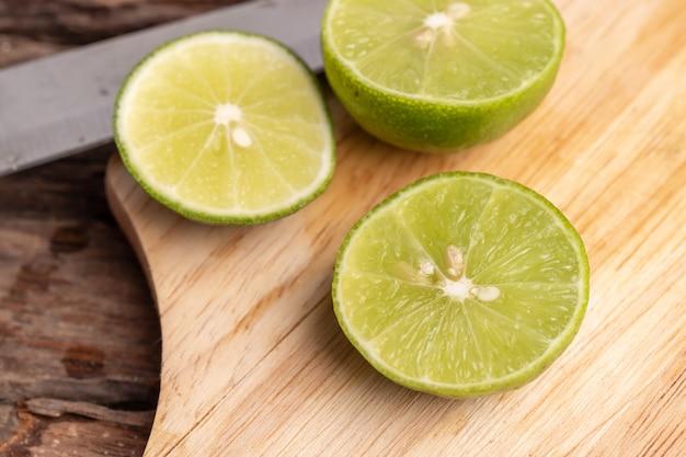 Metade do limão verde e sementes com um lugar de faca na placa de madeira Foto Premium