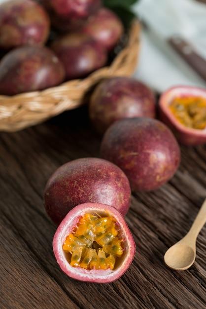 Metade do maracujá e do passionfruit orgânico na cesta de madeira, fundo de madeira. Foto Premium