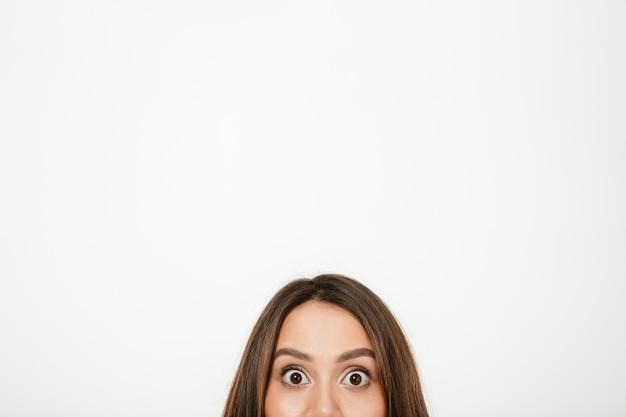 Metade do rosto de mulher morena surpresa, olhando para a câmera sobre cinza Foto gratuita