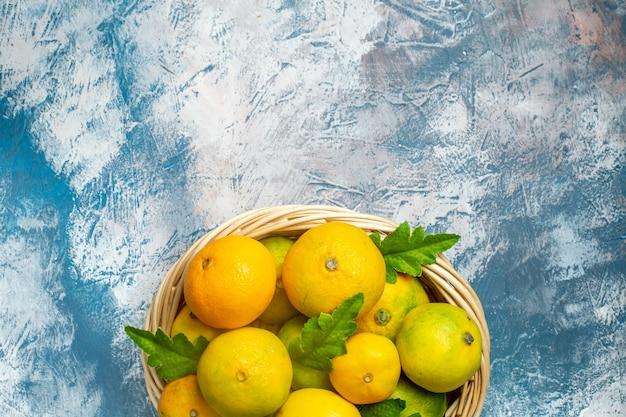 Metade superior vista tangerinas frescas em vime baske em espaço livre de superfície branco azul Foto gratuita