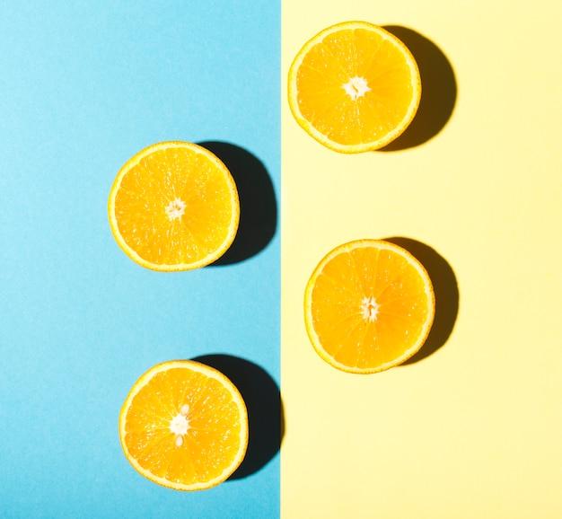 Metades de laranjas em fundo azul e amarelo Foto gratuita