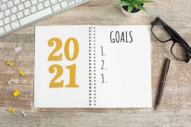 Metas de ano novo listam 2021 na mesa de madeira. Foto Premium