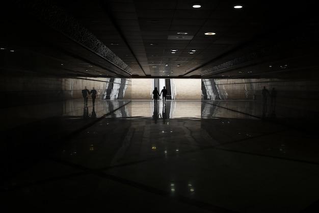 Metrô escuro com pessoas andando à distância Foto gratuita