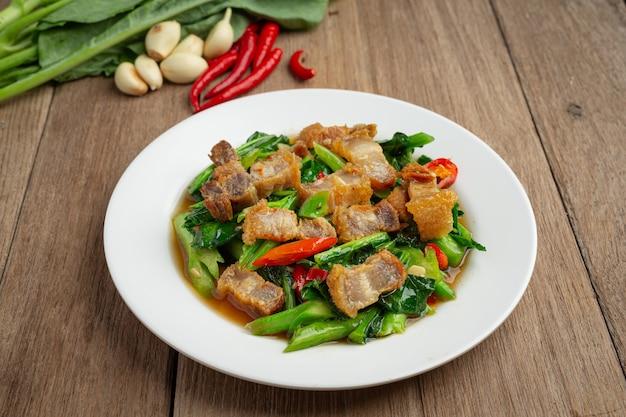 Mexa couve frita, carne de porco crocante picante na mesa de madeira conceito de comida tailandesa. Foto gratuita