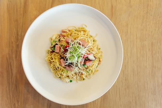 Mexa o macarrão chinês frito com presunto e carne de caranguejo no fundo da mesa de madeira Foto Premium