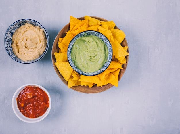 Mexicano guacamole dip e nachos chips de tortilla com molho em taças Foto gratuita