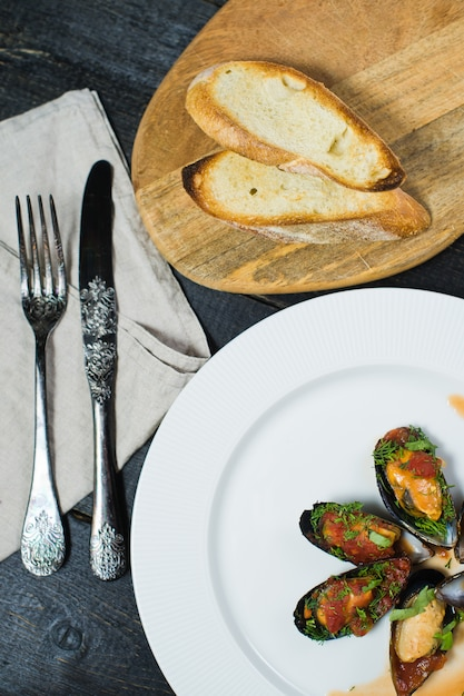 Mexilhões cozidos no molho de tomate com coentro e parmesão em uma placa branca. Foto Premium