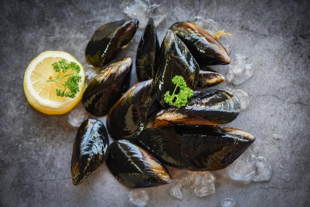 Mexilhões crus com ervas limão e fundo escuro - frutos do mar frescos frutos do mar no gelo no restaurante ou à venda no mercado mexilhão alimentos Foto Premium