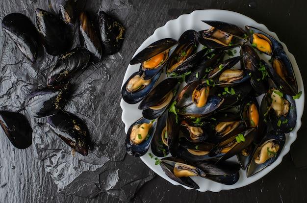 Mexilhões crus e cozidos frescos no fundo preto da pedra da ardósia. conceito de frutos do mar. vista do topo Foto Premium