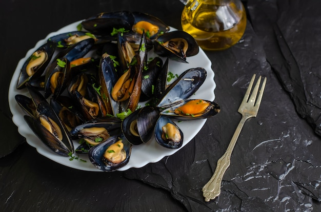 Mexilhões de frutos do mar cozidos deliciosos com ervas e azeite em um prato branco sobre fundo preto. cozinha mediterrânea Foto Premium