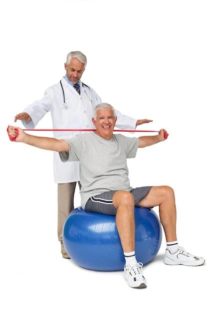 Mhysiotherapist, olhar, homem sênior, sente-se, ligado, exercite-se bola, com, correia ioga Foto Premium