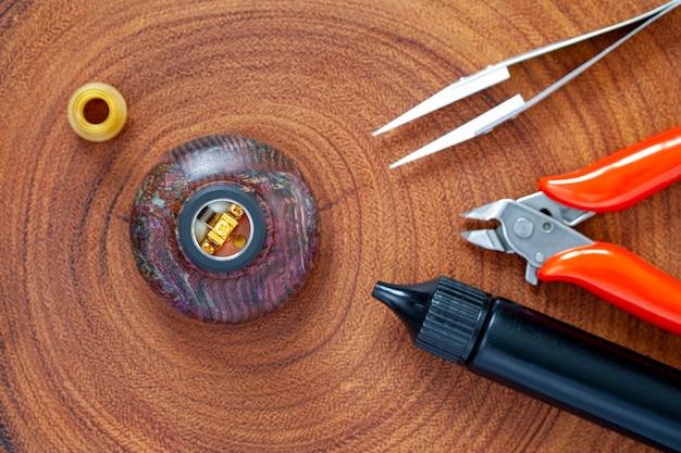 Micro bobina única com algodão no atomizador de gotejamento reconstrutível em suporte de madeira estabilizado com ponta de gotejamento ultem, pinça de cerâmica, alicate de corte Foto Premium