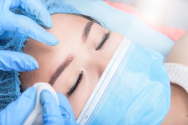 Microblading sobrancelhas fluxo de trabalho. maquiagem permanente para sobrancelhas com tatuagem sobrancelha profissional no salão de beleza. Foto Premium