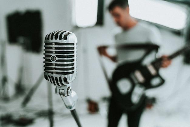 Microfone condensador de diafragma grande com um músico segurando uma guitarra elétrica em background Foto gratuita
