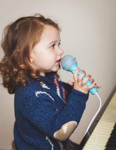 Microfone da criança da menina, do piano e do brinquedo. Foto Premium