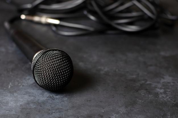 Microfone preto em uma mesa de concreto escura. equipamento para vocais ou entrevistas ou reportagem. copie o espaço Foto Premium