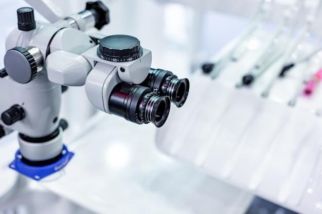 Microscópio dental no fundo da odontologia moderna. equipamento médico. microscópio cirúrgico odontológico com binóculo duplo rotativo. Foto Premium