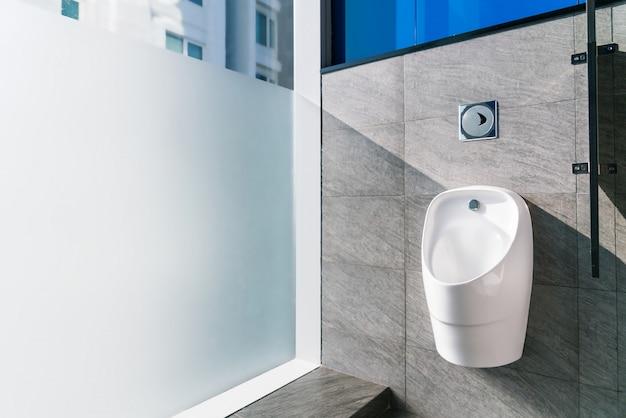 Mictório de cerâmica branca no banheiro masculino Foto Premium