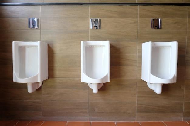 Mictórios brancos no banheiro dos homens da decoração interior. Foto Premium