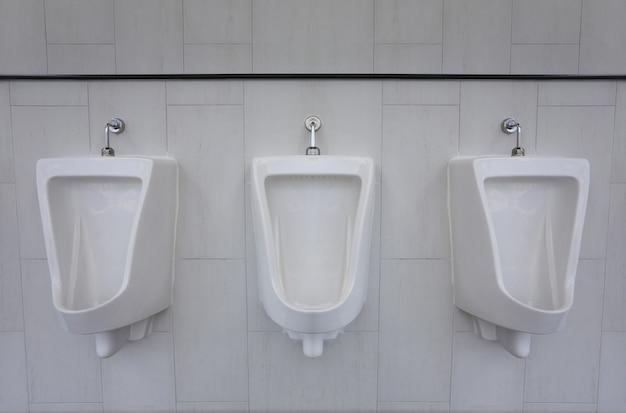 Mictórios brancos no banheiro masculino de decoração de interiores. Foto Premium