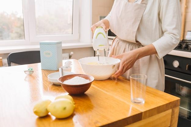 Mid-seção de uma mulher misturando ingredientes para preparar torta na mesa de madeira Foto gratuita