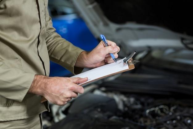 Mid-seção do mecânico de preparar uma lista de verificação Foto gratuita