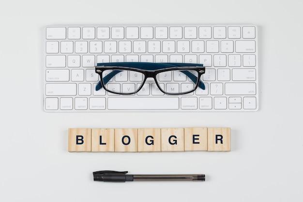 Mídia social e conceito do negócio com blocos de madeira, teclado, óculos, caneta na configuração de plano de fundo branco. Foto gratuita