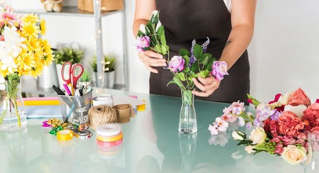Midsection, vista, de, um, mão feminina, ordenando, flores, em, vaso, escrivaninha Foto gratuita