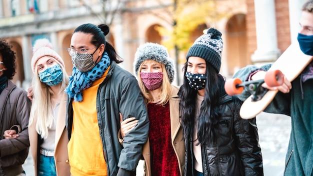 Milenares urbanos caminhando juntos usando máscara no centro da cidade Foto Premium