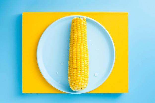 Milho cozido em um prato azul Foto gratuita