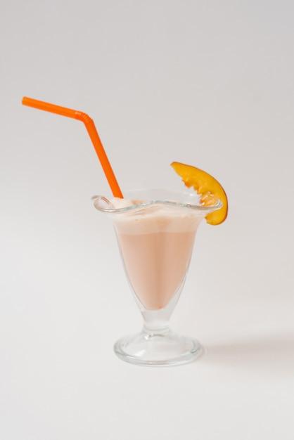 Milk shake com nectarinas em um copo com um tubo de plástico laranja nele sobre um fundo branco. o conceito de comida saudável e deliciosa Foto Premium