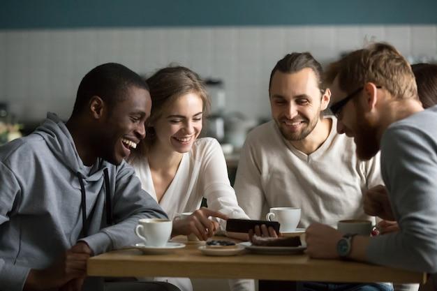 Millennial garota mostrando vídeo móvel engraçado para amigos no café Foto gratuita