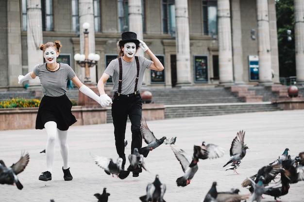 Mime feliz, par, executando, perto, voando, pombos Foto gratuita