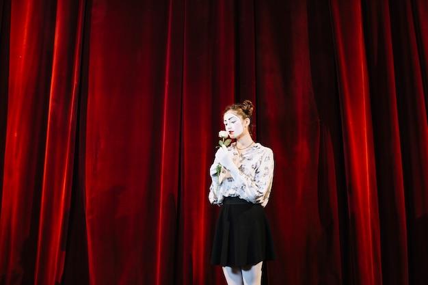 Mime feminino, ficar, frente, vermelho, cortina, cheirando, rosa branca Foto gratuita
