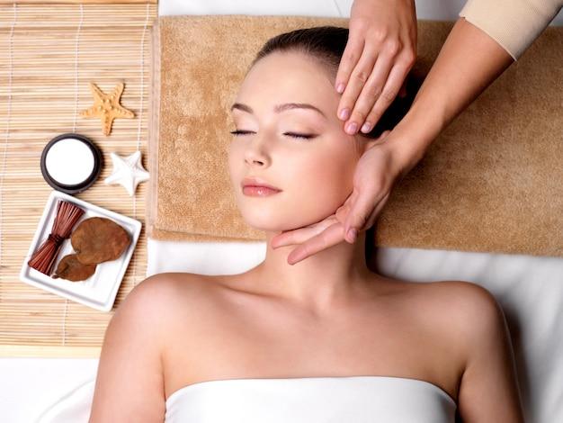 Mimos e massagem para o lindo rosto de uma jovem em um salão de spa Foto gratuita