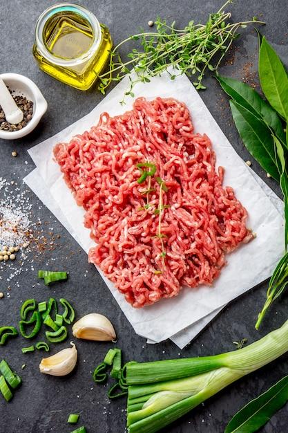 Mince carne à terra com os ingredientes para cozinhar no fundo preto. carne de boi picada. Foto Premium