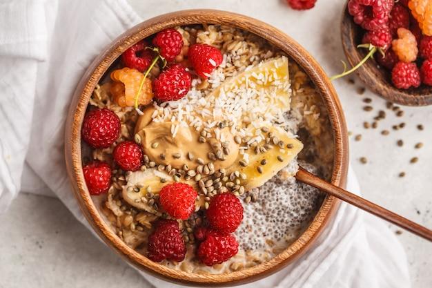 Mingau de aveia com sementes de chia, bagas, manteiga de amendoim e sementes de cânhamo na tigela de madeira, fundo branco. Foto Premium