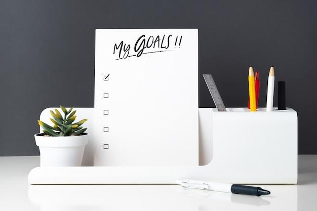 Minha lista de objetivos no bloco de notas em papelaria escritório moderno na mesa branca e cinza escuro Foto Premium