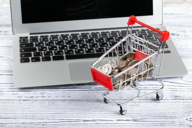 Mini carrinho de compras e laptop Foto Premium