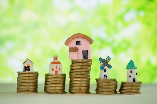 Mini casa na pilha de moedas com borrão verde. Foto gratuita