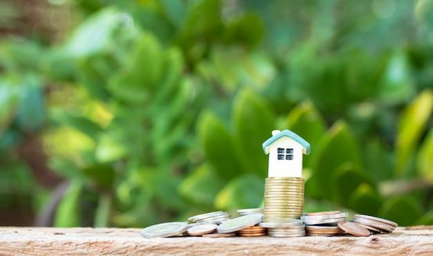 Mini casa na pilha de moedas na natureza turva Foto Premium