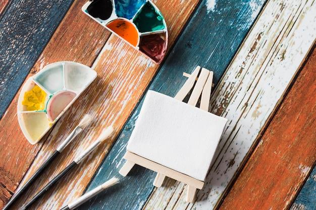 Mini cavalete em branco e equipamentos de pintura na velha mesa de madeira colorida Foto gratuita