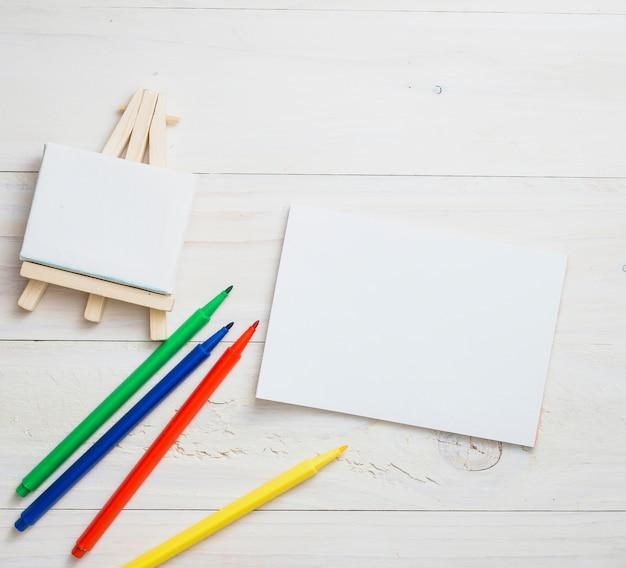Mini cavalete em branco; papel branco e cores caneta de ponta de feltro sobre o pano de fundo de textura de madeira Foto gratuita