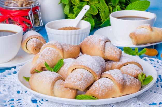 Mini croissants com damascos secos, figos e nozes em um prato com uma xícara de café Foto Premium